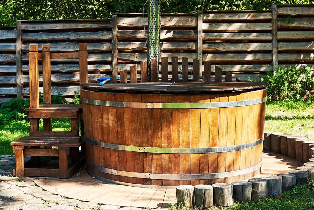 Modern wooden hot tub with stairs in garden outdoor