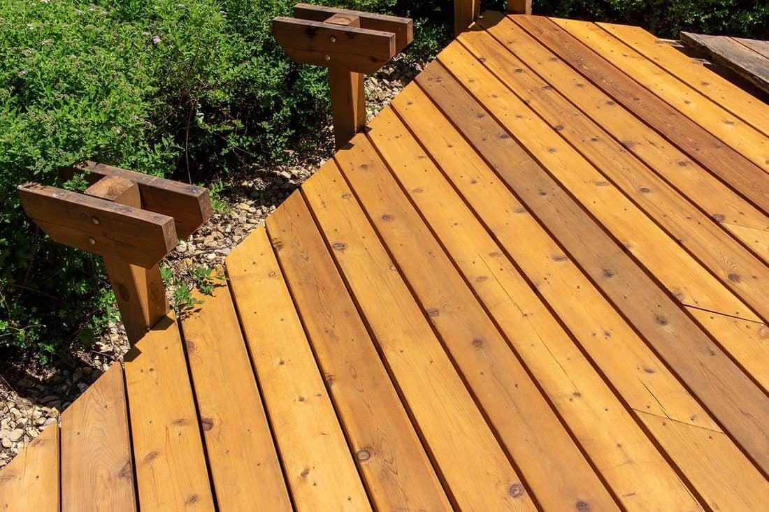 Newly restored exterior cedar deck in progress on a sunny day