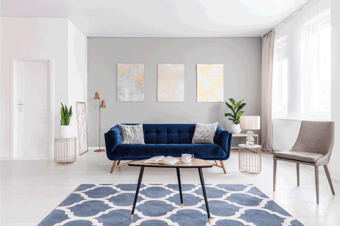 Open-plan living room interior with modern furniture made of dark blue sofa, beige armchair, coffee table and other items in gold color
