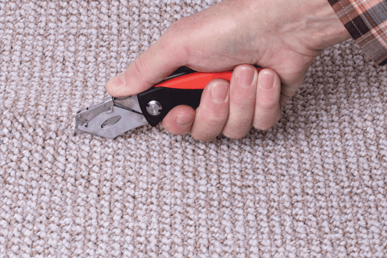 People-in-handyman-jobs.-The-hand-of-a-craftsman-cuts-a-carpet-with-cutter.-How-To-Use-A-Carpet-Cutter-Or-Trimmer-[A-Complete-Guide]