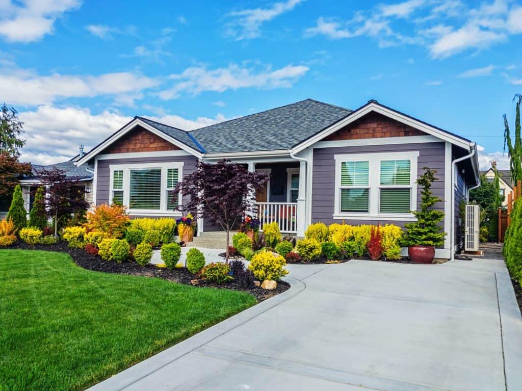 Photo of a modern custom single-level suburban home on a sunny summer day