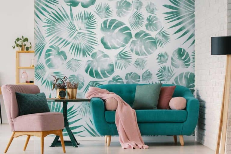Pink armchair and blue settee in living room interior with green wallpaper and lamp, Does Wallpaper Cover Cracks And Imperfections?
