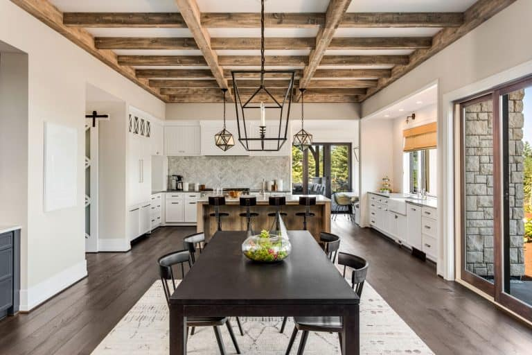 Rustic contemporary kitchen interior designed with a black dining table and chairs incorporated with protruding ceiling beams, How Wide Should Ceiling Beams Be?