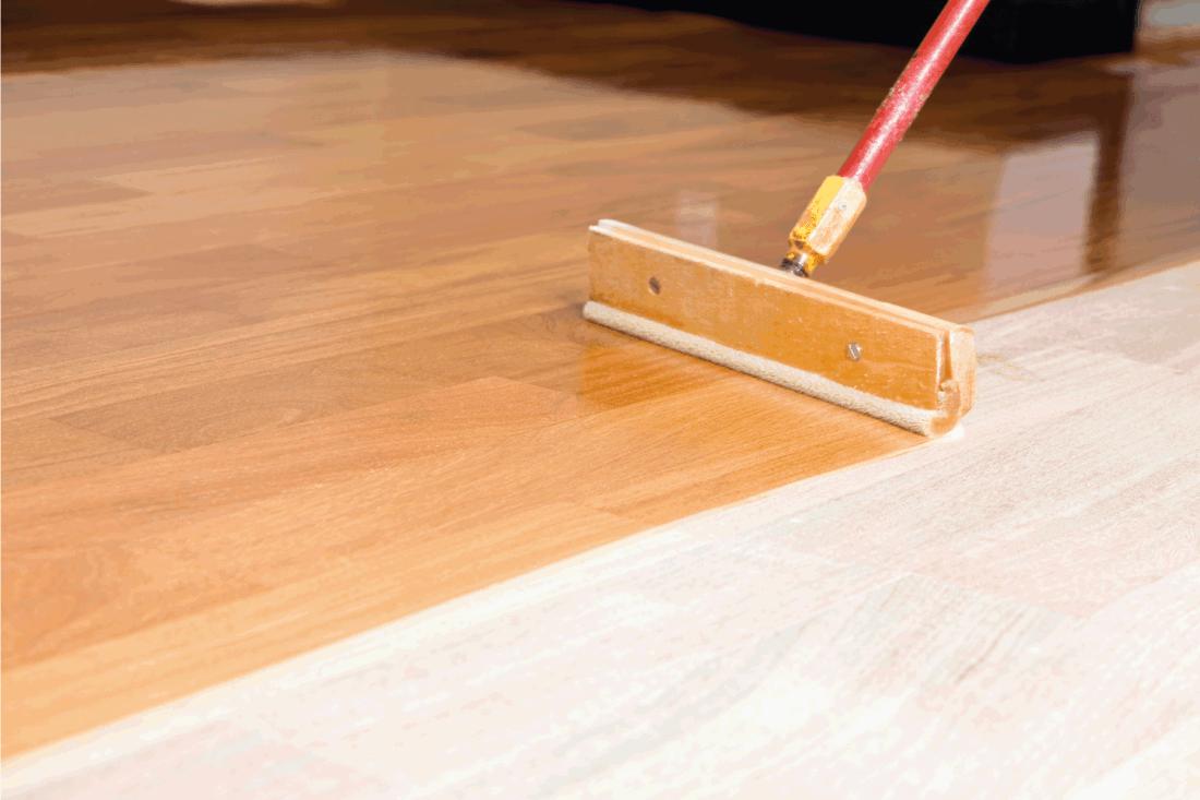 Squeegee Style Brush Applying Clear Polyurethane to Hardwood Floor