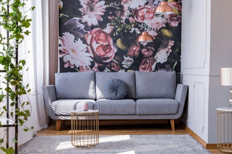 Sunlit, gray sofa by a floral print wall in the nook of a feminine living room interior with golden accessories, Does Wallpaper Make A Room Look Bigger Or Smaller?