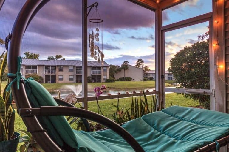 Swinging lounge chair on a lanai at sunset, How Long Should A Lanai Screen Last?