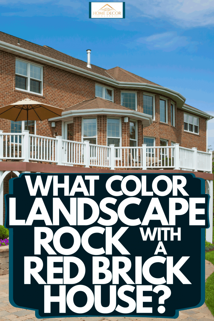 Huge two storey luxurious mansion with red brick walls, white fence dock area, and gorgeous landscaping, What Color Landscape Rock With A Red Brick House?