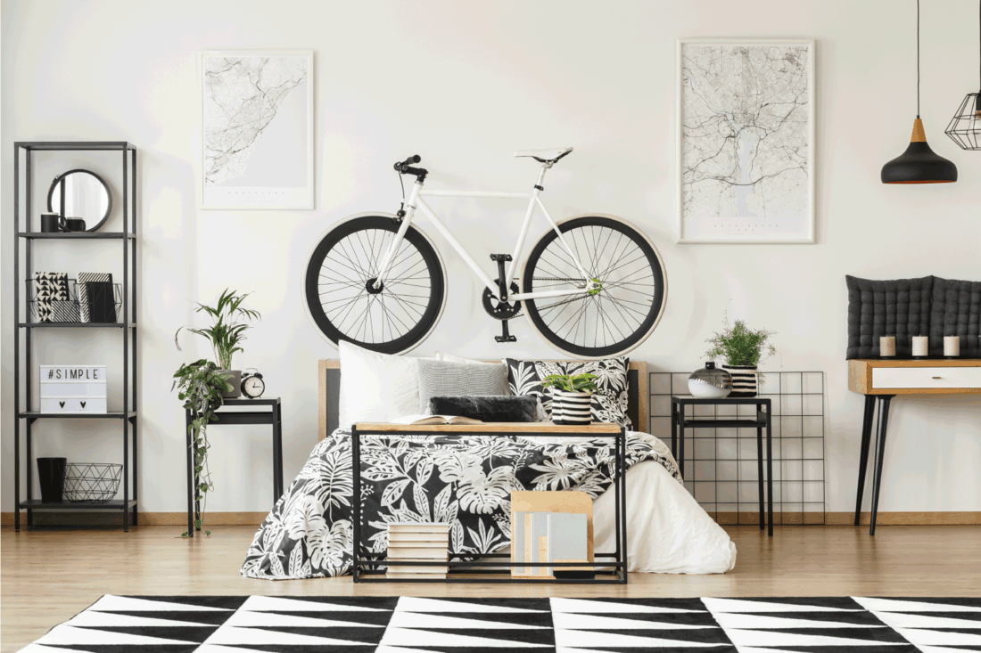 White bike standing on wooden bedhead between map posters in monochromatic bedroom interior for a teenager