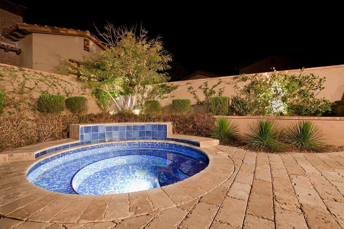 Wide angle shot of a private backyard spa at night
