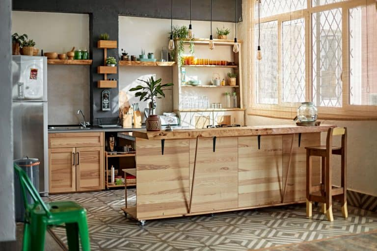 Wide angle view of unoccupied kitchen using rustic style wooden materials for cabinets, shelving, and kitchen island, 10 Ways To Fill Empty Floor Space In A Kitchen