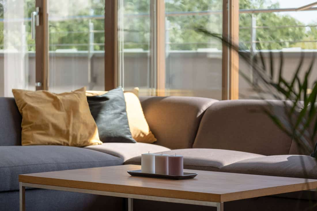 Wooden coffee table and gray corner sofa in living room with window wall