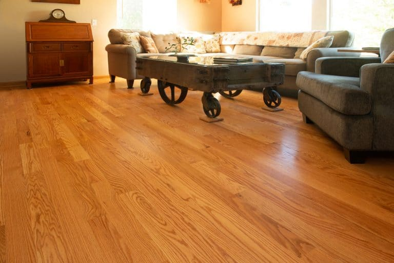 Wooden flooring living room with a wheeled coffee table and gray color sofas, Should Hardwood Floors Change Direction?