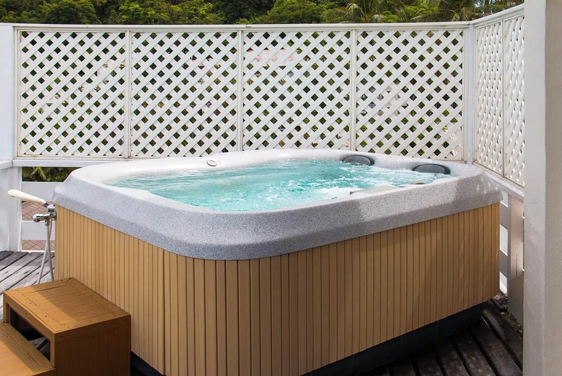 Wooden hot tub with swirling water at outdoor