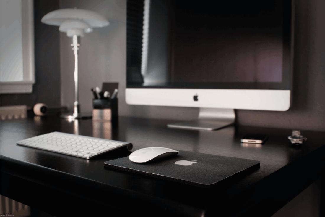 black wood desk with computer set on top