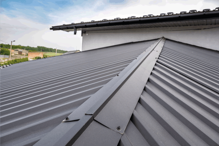 close up photo of gray colored roofing on a house. What Color Metal Roof Fades The Least
