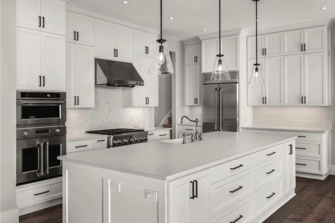 Beautiful kitchen in new luxury home with island, pendant lights, and hardwood floors. Features stainless steel appliances, including double oven, refrigerator, gas range and hood.