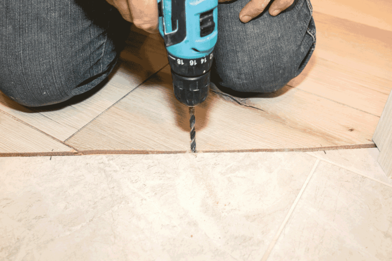 man-using-hand-drill-to-prepare-floor-for-transition-strip-installation.-12-Types-Of-Flooring-And-Carpet-Trims-And-Transitions