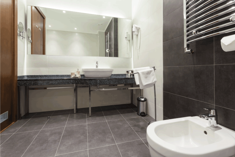 modern bathroom with gray floor tiles, white wall tiles, double vanity. What Color Grout To Use With Gray Tile