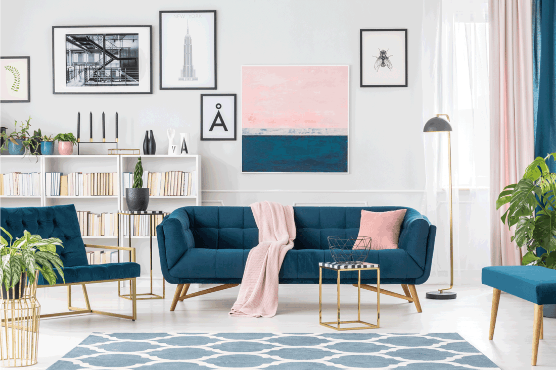 modern living room interior with a feminine flair, blue couch, pink accent