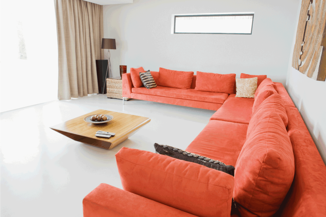 modern living room with orange long couch and a wooden coffee table in the middle