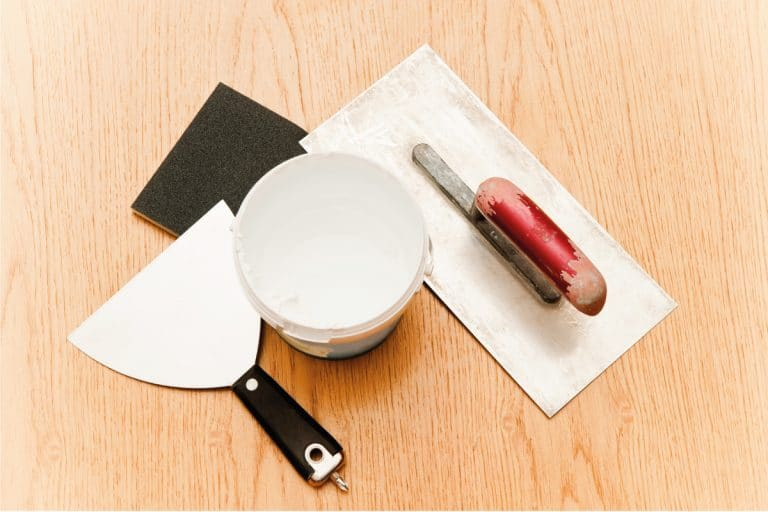 putty knife, trowel, and open putty jar on top of hardwood floor. How To Fix Holes In Hardwood Floor - Large And Small!