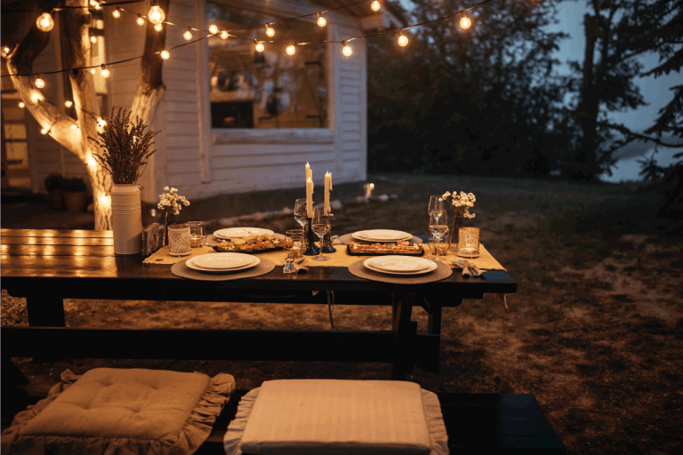 Shot of a nicely set table awaiting guests for dinner in a backyard with hanging string lights from a tree. How To Hang String Lights In A Lanai