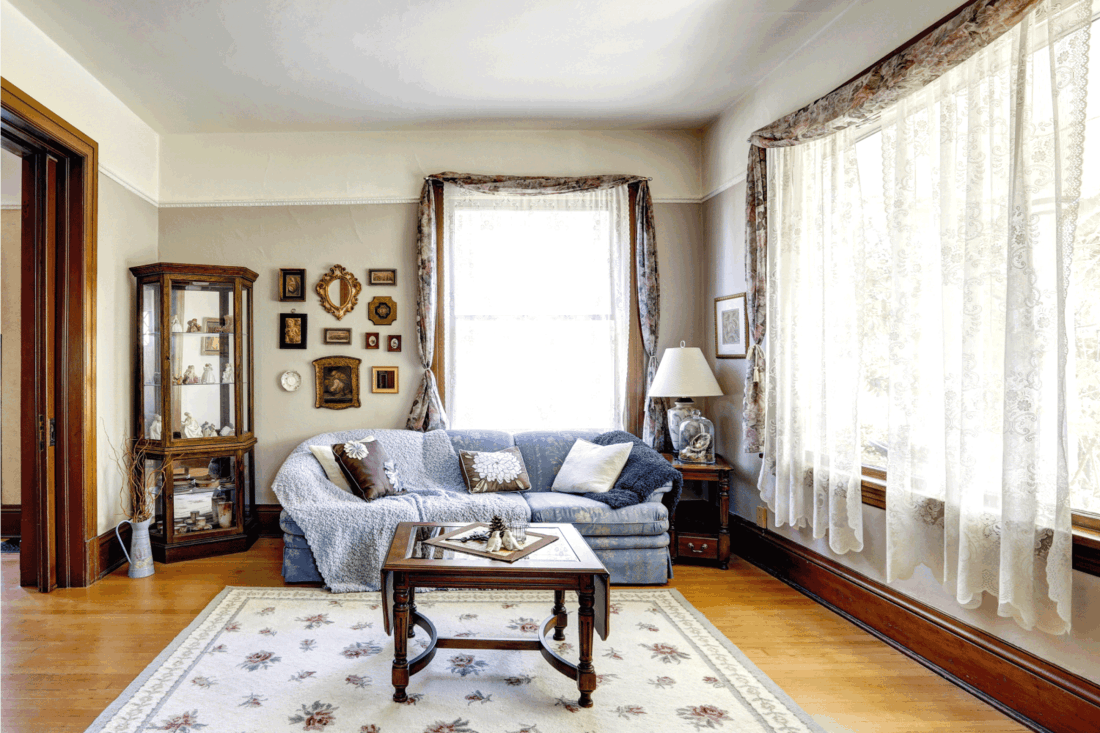 tried true traditional living room with bright windows, blue couch, display casing at the corner