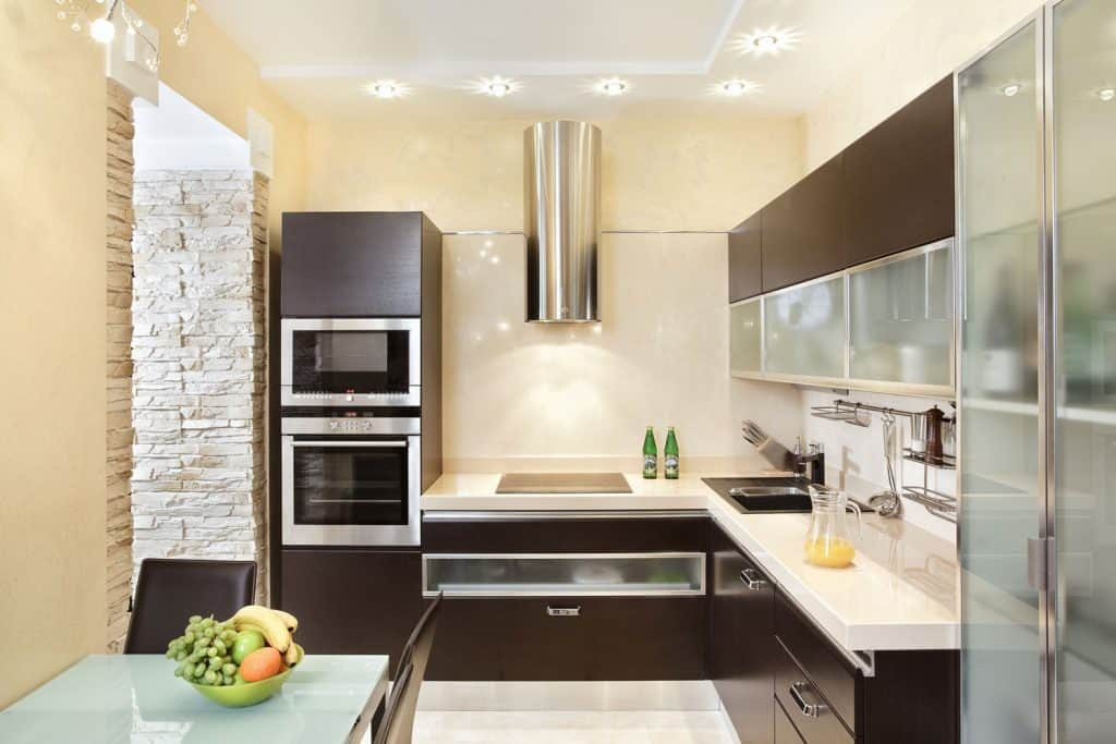 A beige painted kitchen wall with modern kitchen appliances and drawers