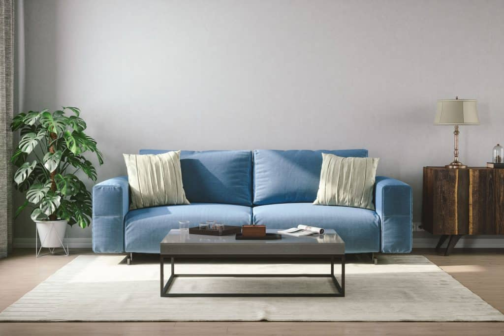 A blue colored sofa with throw pillows and a properly spaced coffee table