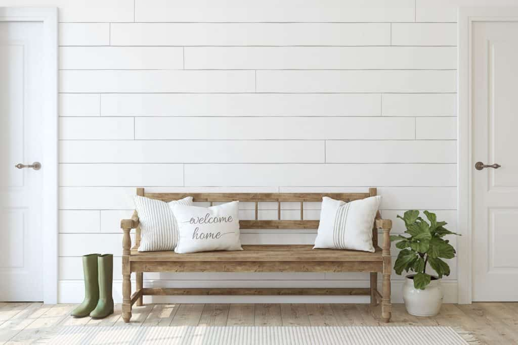 A bohemian inspired living room with shiplap wall design and a wooden sofa with throw pillows