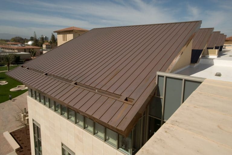 A brown pre-painted metal roof of a luxurious residential house, What Color House Goes With A Metal Roof?
