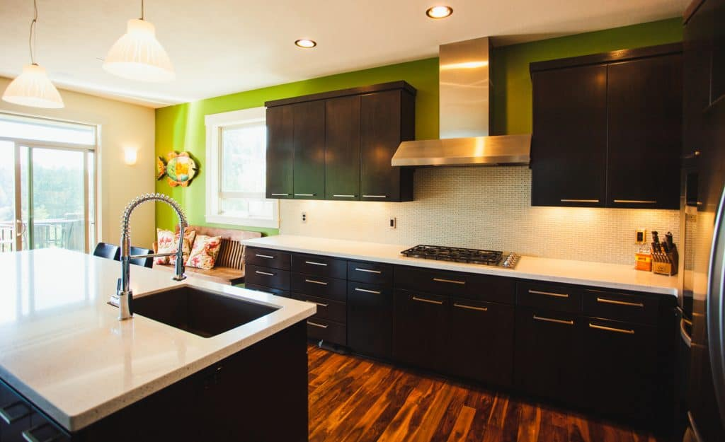 A clean spacious modern home kitchen with black cabinets.