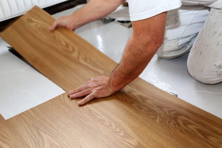 A flooring specialist installing a vinyl flooring in the living room, Vinyl Plank Flooring Shrinkage - What To Do?