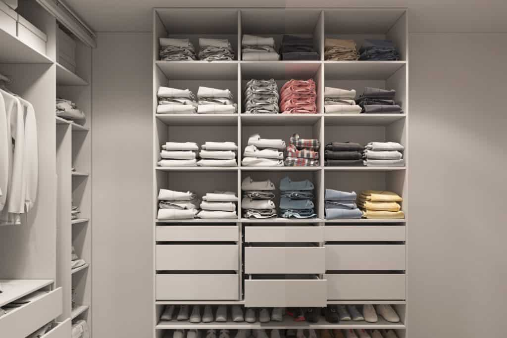 A gorgeous walk in closet with folded shirts and shoes underneath