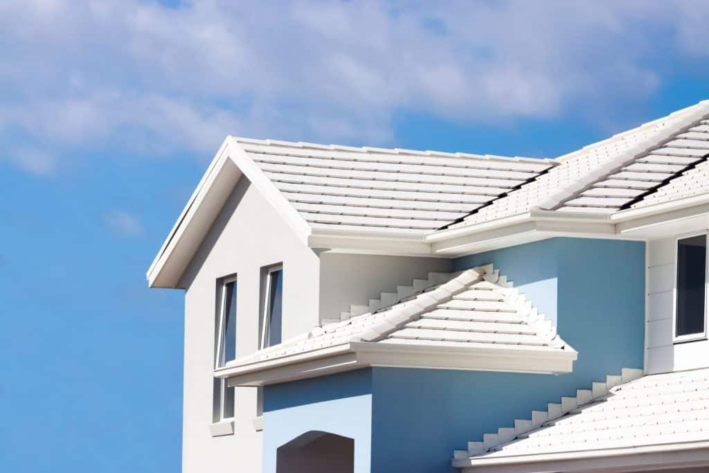 A gorgeous white and blue colored house with white shingle roofing
