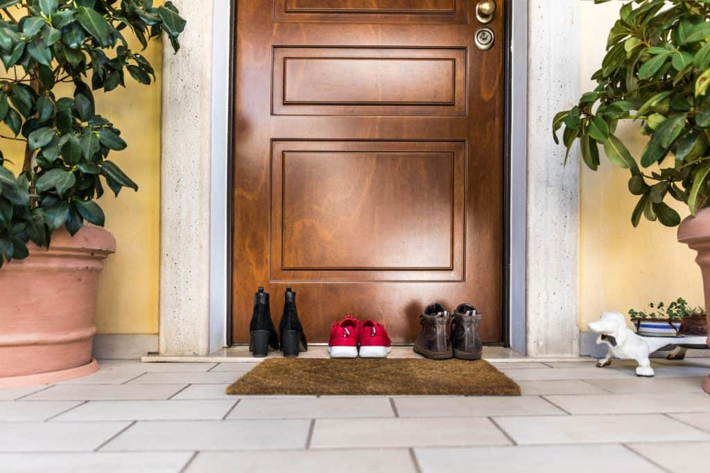 A hardwood front door with shoes laid on the front