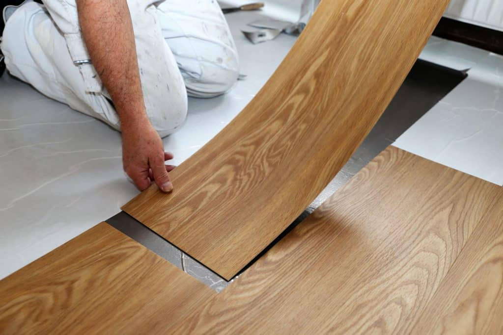 A man installing vinyl flooring inside the living room
