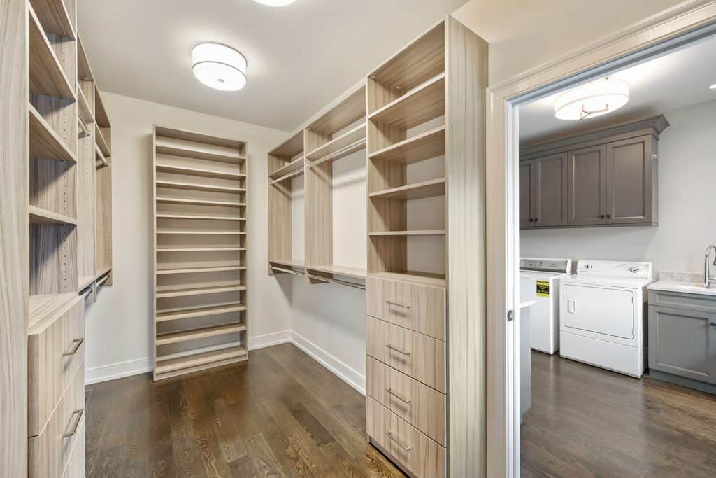 A narrow wooden fabricated walk in closet with hardwood flooring and a round white lamps