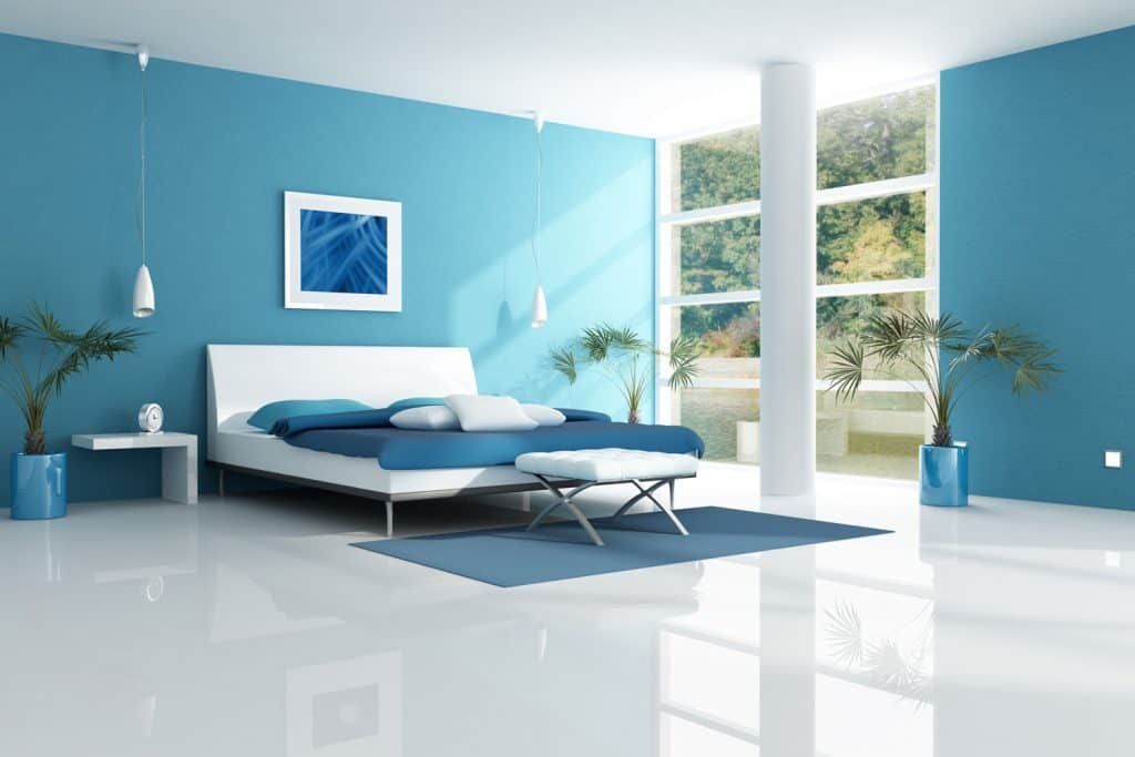 A spacious bedroom with blue painted walls, white granite flooring and plants for diversity