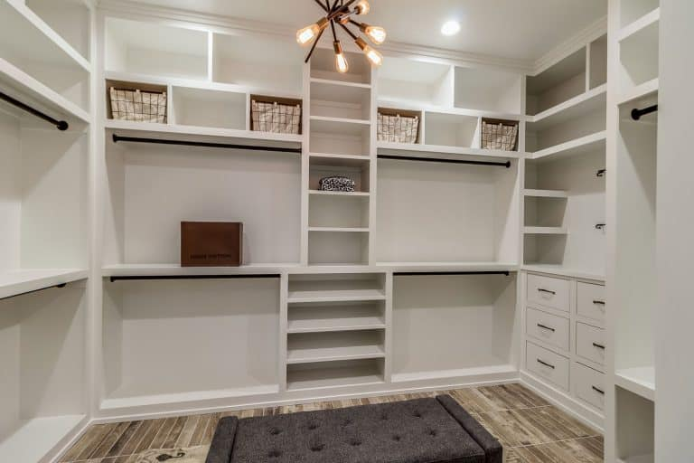A spacious walk in closet with an abstract looking chandelier, What Color Should You Paint Closets?