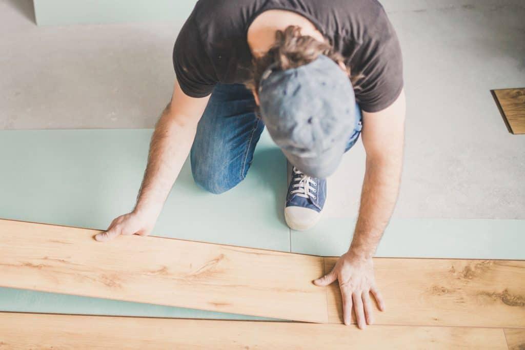 A tile setter placing a vinyl plank flooring