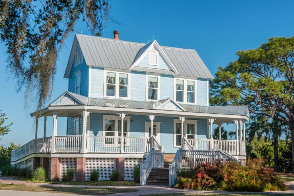 A two storey American country home with blue painted walls and a grey painted roofing