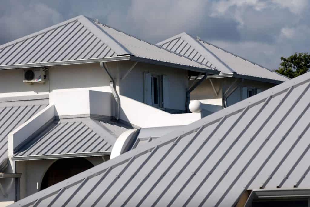A two storey mansion with light gray painted roofing and white painted walls