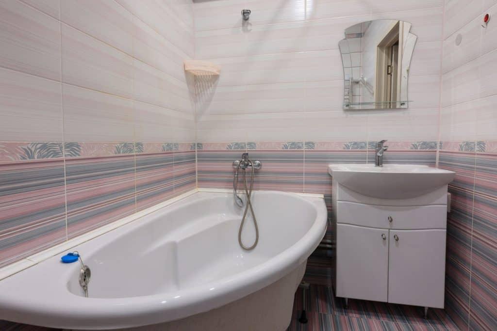A white ceramic bathtub inside a narrow bathroom