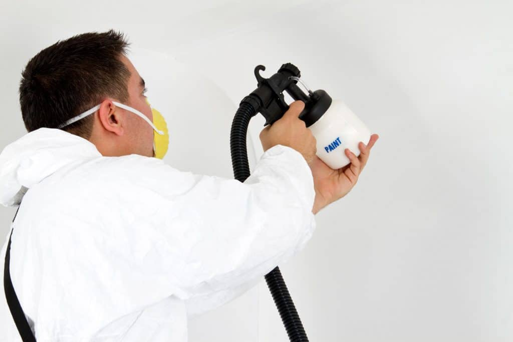 A fully suited worker spraying the room with white