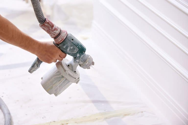 A worker using a sprayer to paint the room white, How To Paint A Room With A Sprayer