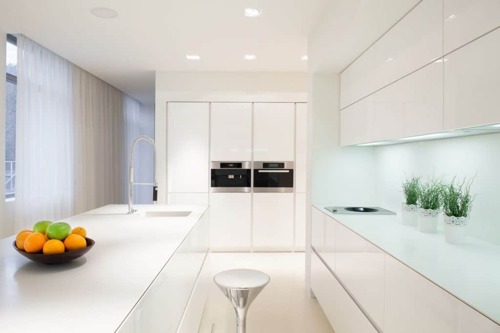 An ultra luxurious kitchen with white cabinets, plants and recessed lighting