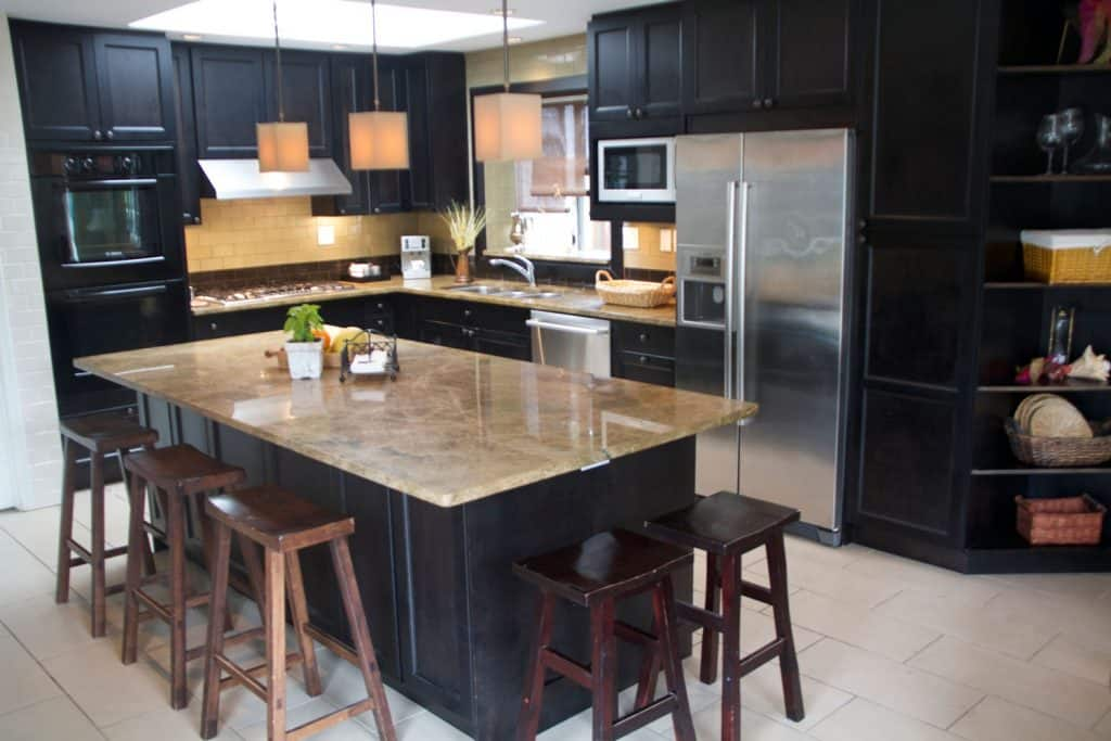 Black painted wooden cabinetries and brown countertops on the breakfast bar and sink area