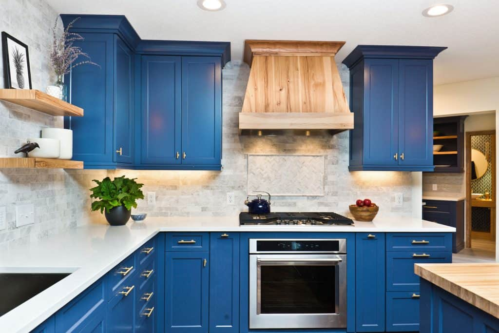 Blue colored kitchen cabinetries incorporated with white countertop, indoor plants and a wooden covered hood