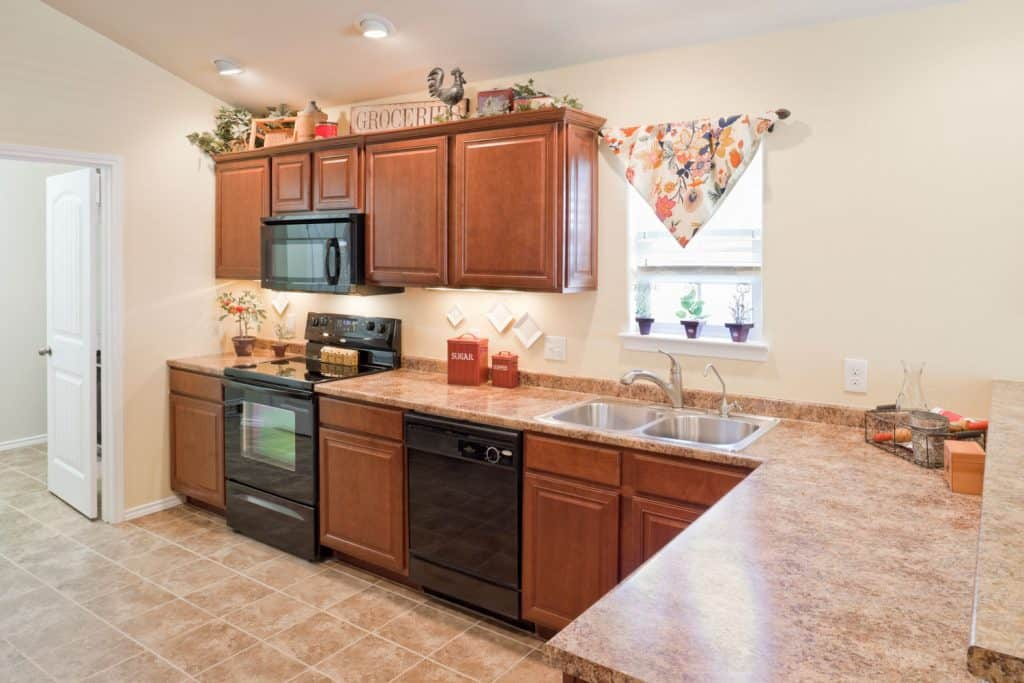 Brown marble countertop incorporated with oak cabinetries and brown tiles